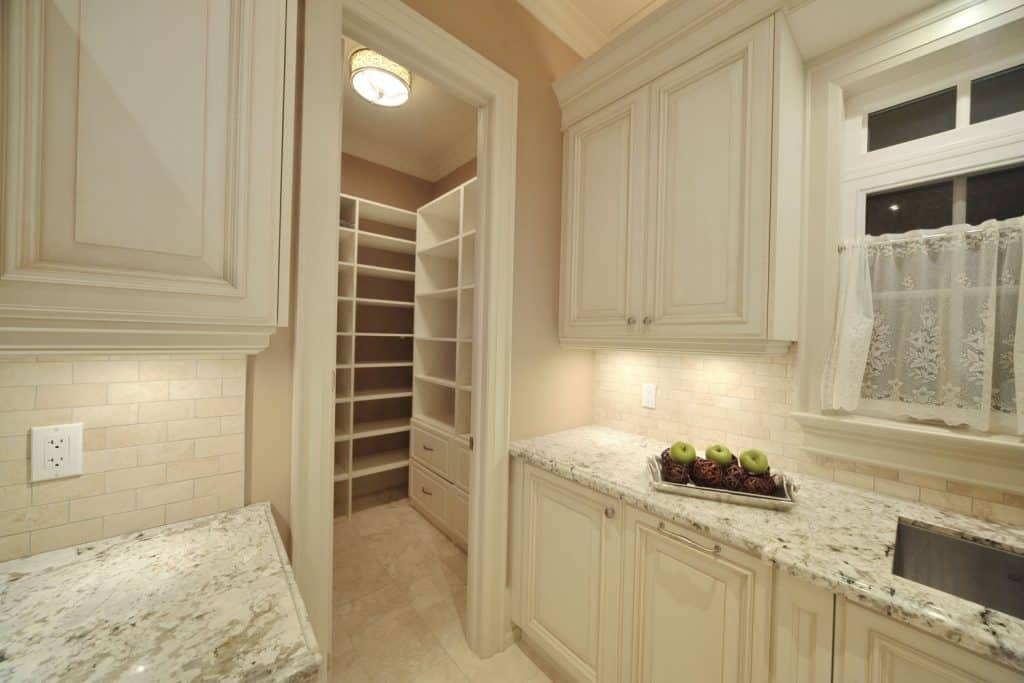 Elegant interior of a kitchen pantry incorporated with the color beige and marble countertops
