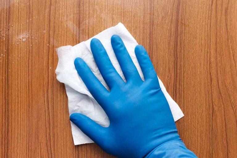 Hand wearing blue glove wiping oak door, How To Get Oil And Grease Marks Off Oak Doors