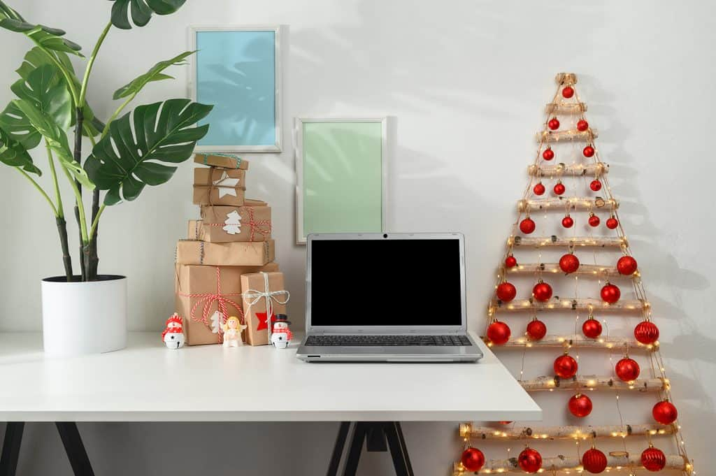 Laptop and gifts on a white desk, a Christmas tree from branches in a home office