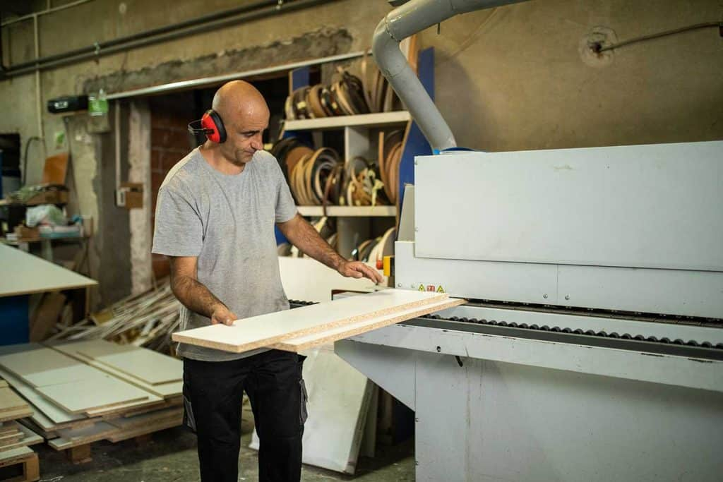 Manual worker using veneer machine in in woodworking company
