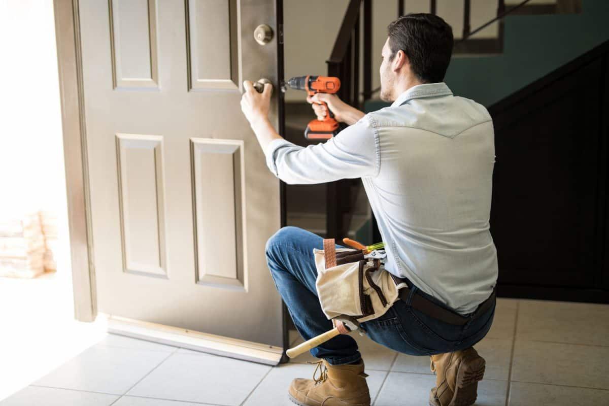 White wooden interior door, metallic circle doorknob and lock with the defocused living room