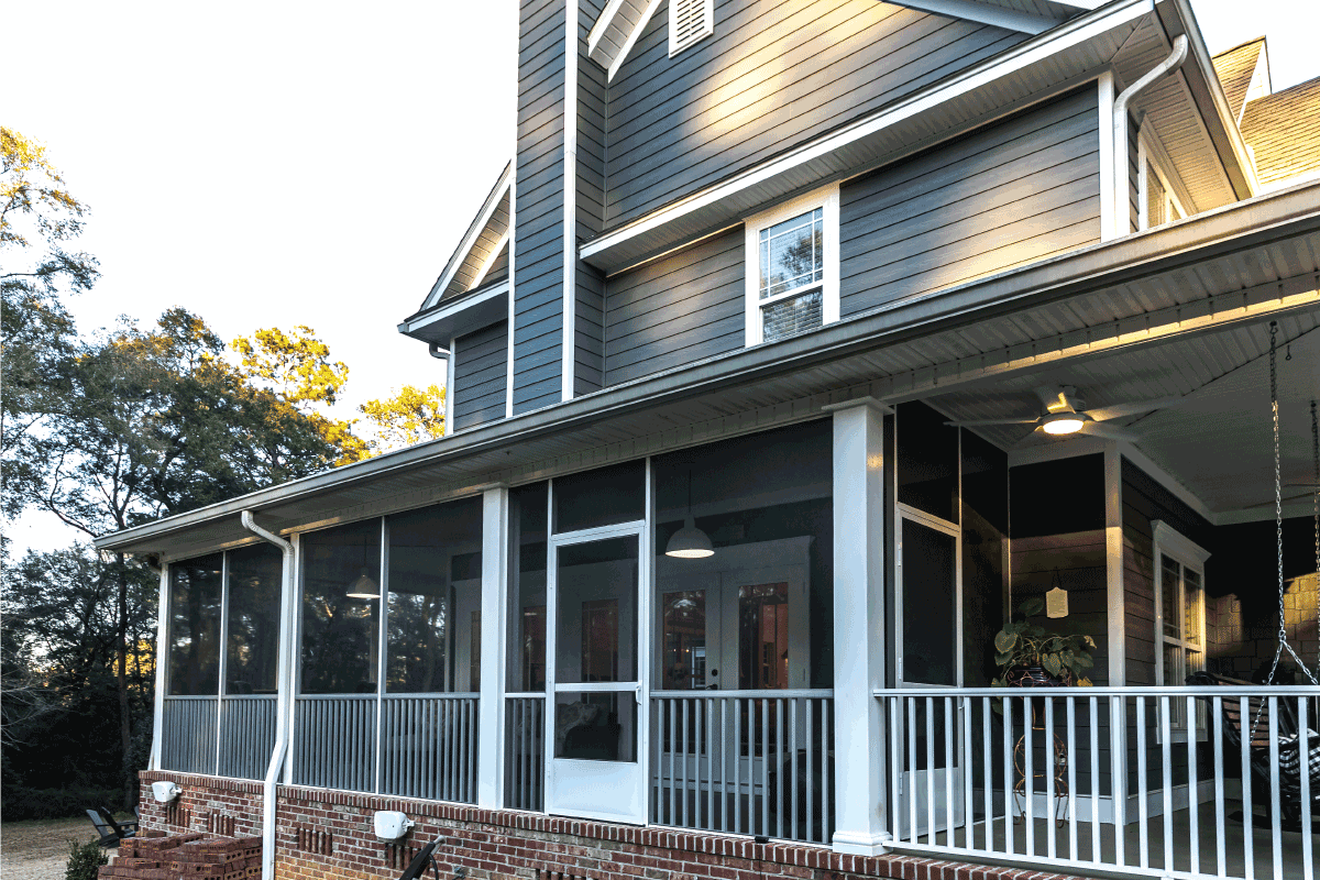 Side view of a large two story blue gray house with wood and vinyl siding, screen door. Do Screen Doors Need Frames