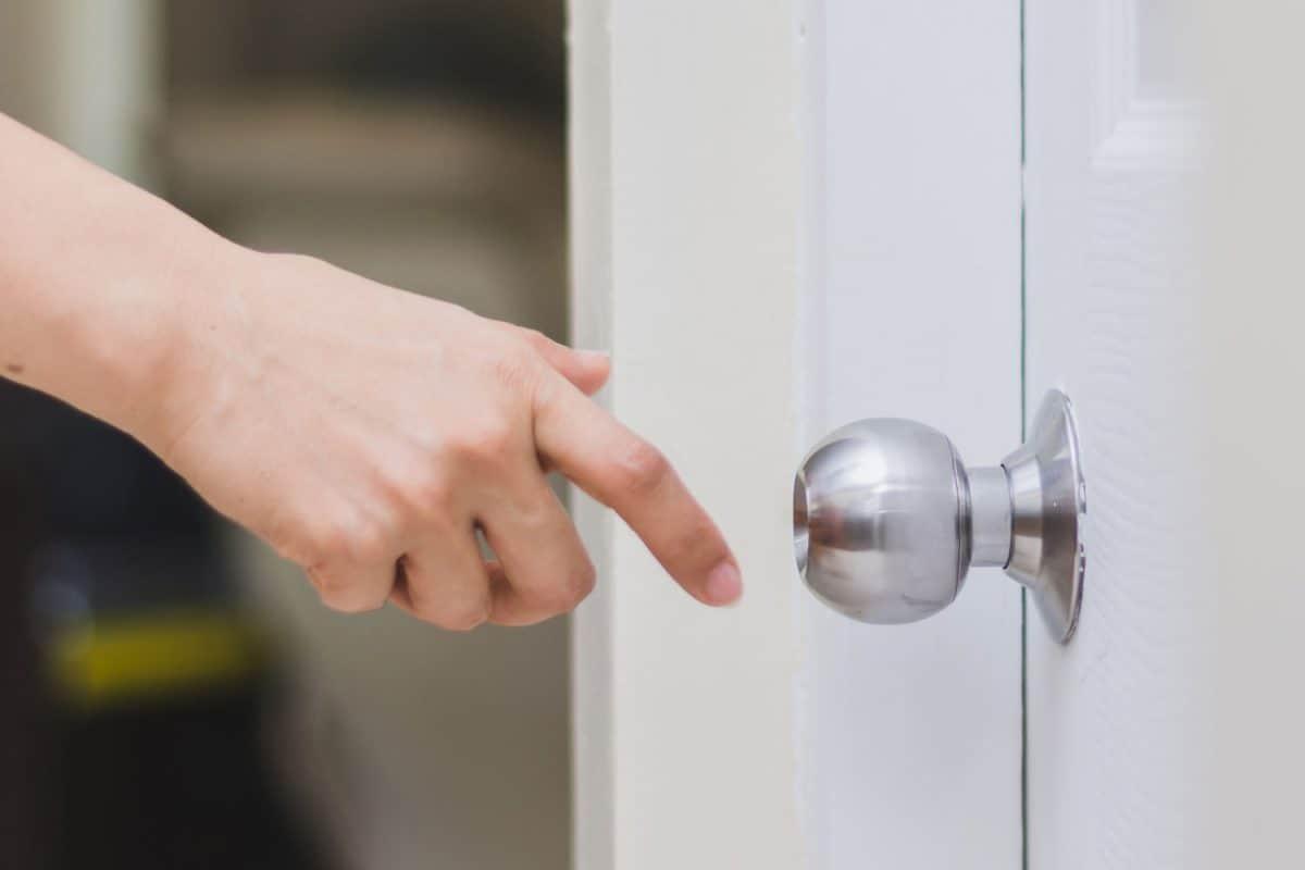close up of woman's hand reaching to door knob, opening the door