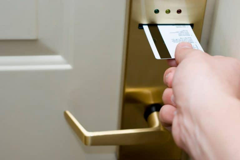 A woman inserting a card for the hotel room door, Magnetic Door Lock System Not Working - What To Do?