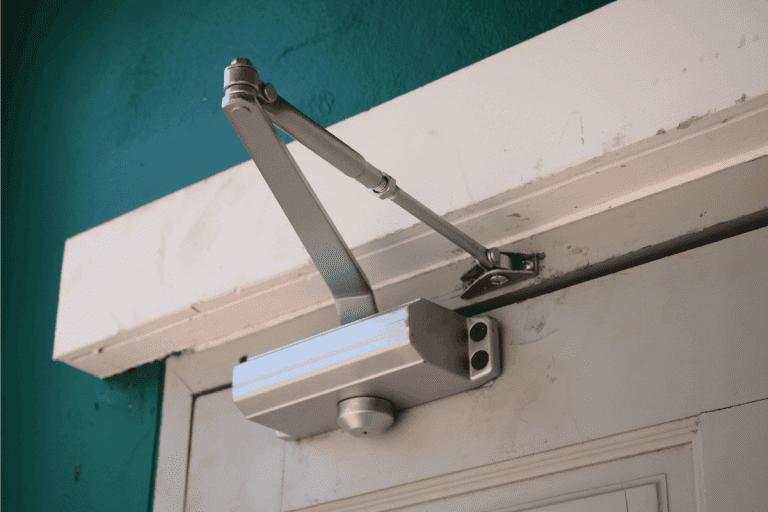 Automatic door closer holder attached to a wooden door and door jamb. How To Install A Door Closer On A Screen Door