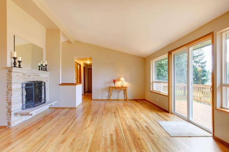 Empty living room with a fireplace and glass sliding door, How To Get A Sliding Door To Slide Easier?
