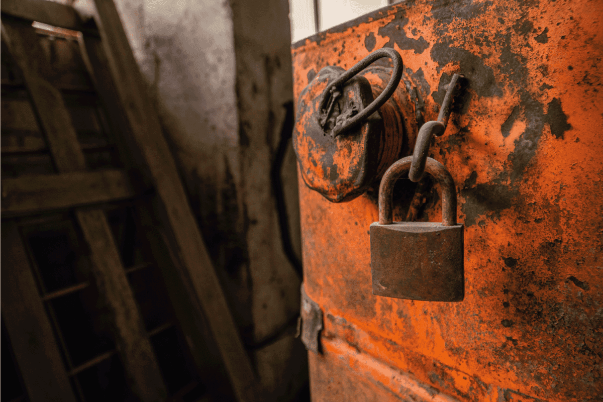 Old rusty padlock on orange fuel tank