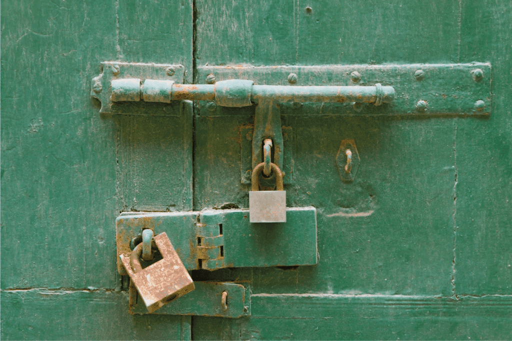 Padlocks And Bolt On green Door. Should You Oil Padlocks [And How To]