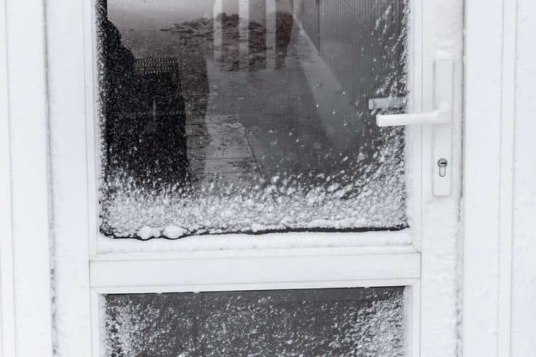 White front door is covered with snow after a blizzard, What Is The Best Material For Storm Doors?