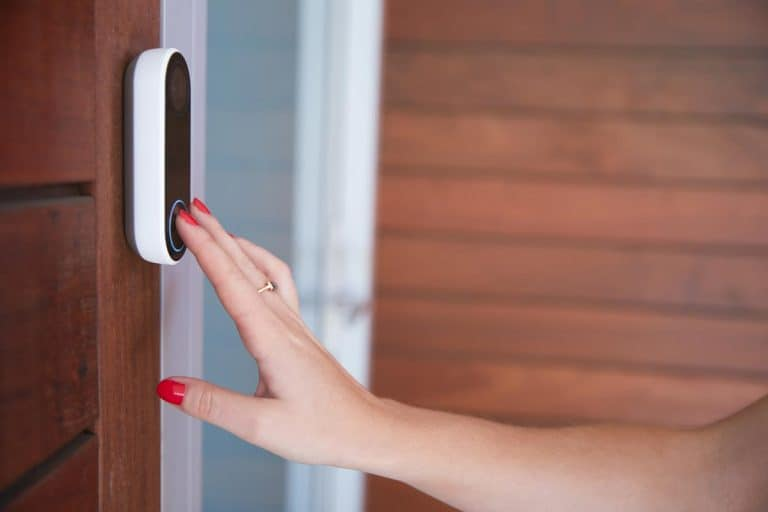 Woman ringing front doorbell equipped with security video camera, 3 Types Of Doorbells