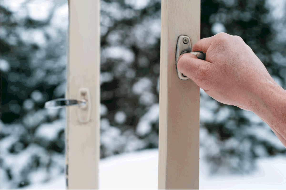 mans hands opening a screen door from the inside