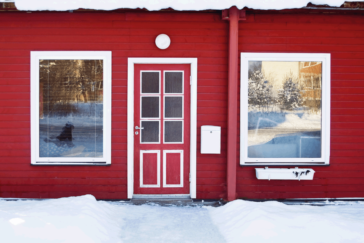 red front door on a red house in wintertime