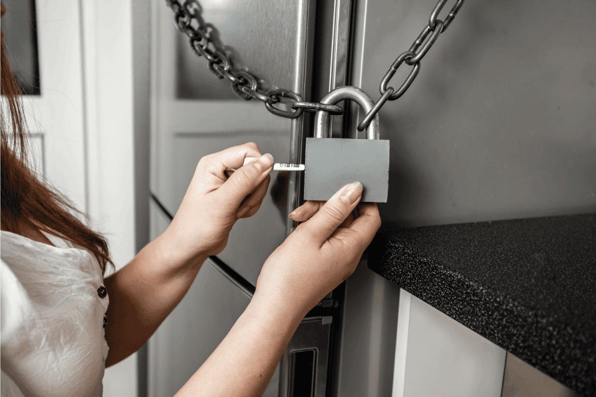 woman installing hanging lock on refrigerator